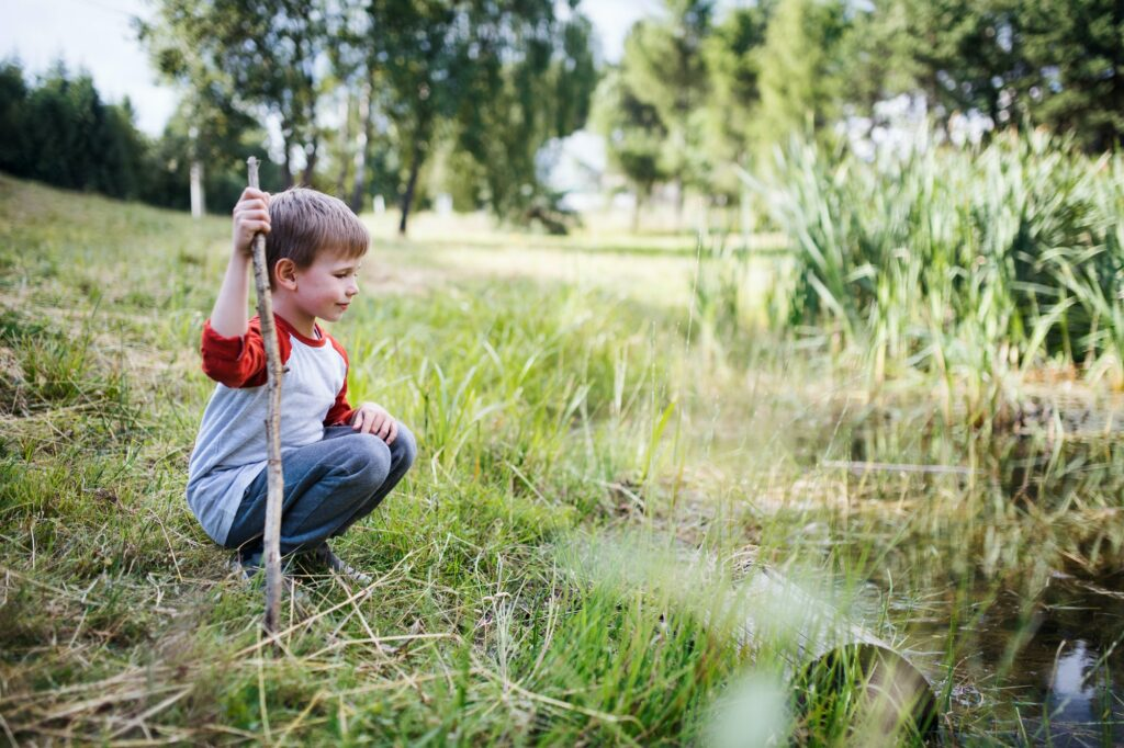 Portrait of school child on field trip in nature, looking at pond
